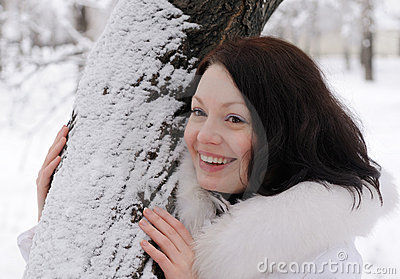 Portrait of the young woman in white at a tree