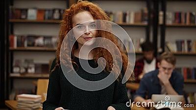 Portret atrakcyjnej, długiej czerwonej, europejskiej studentki stojącej w licealnej bibliotece uśmiechającej się patrząc na zbiory
