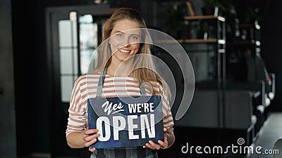 Portret atrakcyjny blond kelnerki mienie otwarty podpisuje wewnątrz nowy cukierniany ono uśmiecha się zbiory