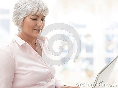 Uśmiechnięta starsza kobieta pracuje na laptopie