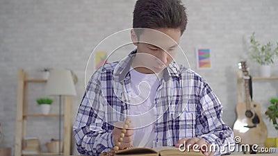 Portret jonge Aziatische mens met een rozentuin in zijn hand die een Bijbel lezen stock footage