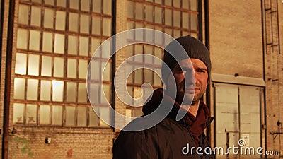 Portret mężczyzny chodzącego po budynkach przemysłowych i zachodzie słońca zbiory