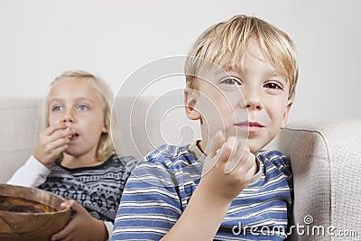 Portret młoda chłopiec z siostrzanym ogląda TV i jeść popkornem