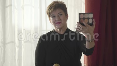 Portret pięknej dojrzałej kobiety przyklejającej proszek do twarzy pędzlem Zbliżenie atrakcyjnej starszej pani robiącej makijaż zbiory wideo