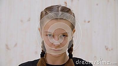 Portret serieus meisje tiener die op camera in lichtstudio kijkt Sluit het gezicht van boos tiener meisje dat de camera vooraan z stock video
