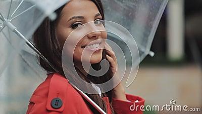 Portret uśmiechnięta kobieta pod parasolem w mieście patrzeje w kamerę Wiosny lub jesieni dzień zbiory wideo