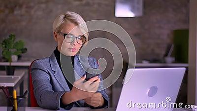 Portret van blonde kortharige onderneemster die op middelbare leeftijd in glazen selfie-foto maken die cellphone in bureau gebrui stock videobeelden