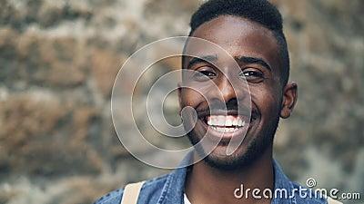 Portret van de close-up het langzame motie van Afrikaans Amerikaans mannetje die met expressief gezicht tonend tanden en bekijken stock videobeelden