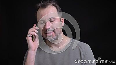 Portret van de geconcentreerde Kaukasische mens op middelbare leeftijd met oorring die emotioneel op smartphone op zwarte achterg stock footage