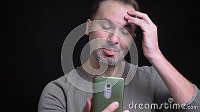 Portret van de geconcentreerde Kaukasische mens op middelbare leeftijd met oorring die vreugdevol in videochat op smartphone op z stock footage