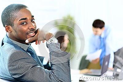 Portret van de glimlachende Afrikaanse Amerikaanse bedrijfsmens met stafmedewerkers
