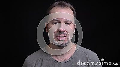 Portret van de Kaukasische mens op middelbare leeftijd met oorring het letten op in camera met verwarring op zwarte achtergrond stock videobeelden