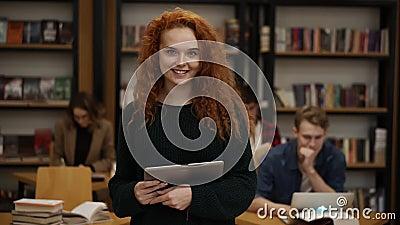 Portret van een aantrekkelijk, langrood geharreld Europees meisje dat in de middelbare schoolbibliotheek staat en glimlacht stock footage