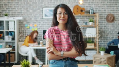 Portret van een aantrekkelijke Aziatische dame die binnen in dienst staat met wapens die door de armen zijn gekruist stock video