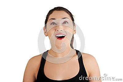 Portret van een gelukkige verbaasde jonge vrouw die omhoog kijkt.