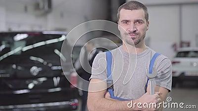 Portret van een knappe kaukasus die naar camera kijkt en glimlacht Professionele automatische werktuigkundige opstelling op de we stock footage