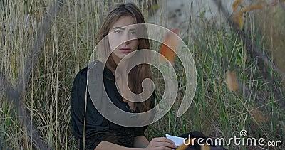 Portret van een mooi Kaukasisch meisje dat in gras zit met een fragment gebroken spiegel en naar de camera kijkt stock video