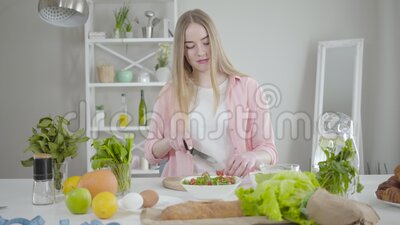 Portret van een positief Kaukasisch meisje dat tomaten snijdt op snijbord en danst Een glimlach-vrouw die graag kookt op stock footage