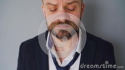Portret van een van streek bebaarde man in ondoorzichtige formele kleding De effecten van het Covid-19-virus op de economie zijn: stock footage