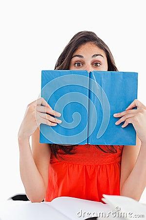 Portret van een student die achter een blauw boek verbergt