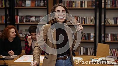 Portret van een vrolijke opgewonden Europese vrouw in jasje en spijkerbroek die expressieve dans uitvoert terwijl ze muziek luist stock video
