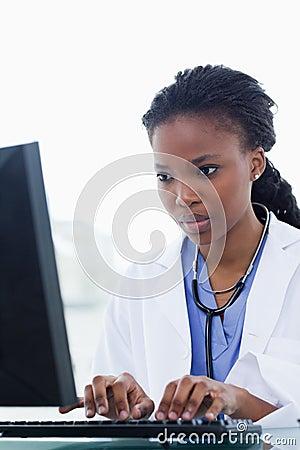 Portret van een vrouwelijke arts die een computer met behulp van