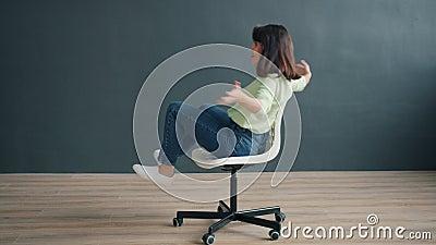 Portret van een zorgeloze dame die op de stoel draait in studio met plezier grappige activiteit met plezier stock videobeelden