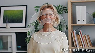 Portret van gelukkige rijpe dame die camera en het glimlachen status in bureau bekijkt stock footage