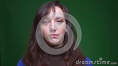 Portret van het jonge donkerbruine vrouwelijke student letten vreedzaam op in camera op groene achtergrond stock videobeelden