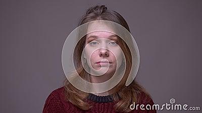 Portret van het jonge vrouwelijke student neigen vreedzaam in camera om met grijze achtergrond goed te keuren en akkoord te gaan stock videobeelden