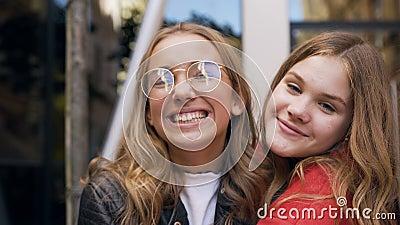 Portret van twee het jonge Kaukasische vrouwenvrienden gelukkig lachen bij camera die elkaar koesteren die van ontspannen levenss stock videobeelden