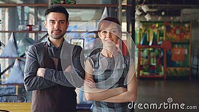 Portret van twee trotse kleine bedrijfseigenaars die zich binnen nieuwe ruime koffie en het glimlachen bevinden Succesvol opstart stock video