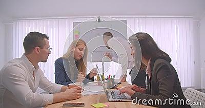 Portret van vier collleagues die en een bespreking over de werkplaats binnen ontmoeten hebben Zakenman die een grafiek trekken stock video