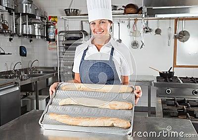 Weiblicher Chef, der gebackene Brote darstellt