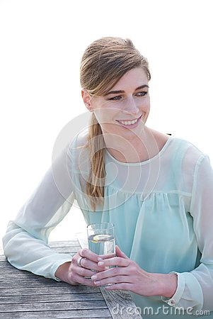 Porträt einer glücklichen jungen Frau, die ein Getränk a genießt