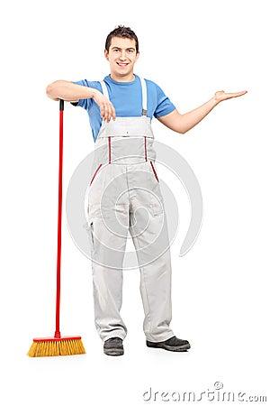 Porträt in voller Länge eines männlichen Reinigers mit einem Besengestikulieren