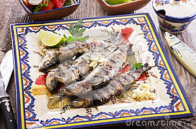 Portuguese grilled sardines as closeup on a traditional plate.