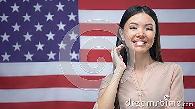 Posição asiática positiva da mulher contra o fundo da bandeira dos EUA, Dia da Independência video estoque
