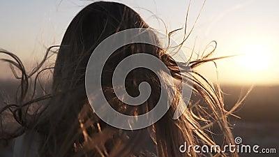 Posição de cabelos compridos da jovem mulher do telefone celular traseiro dos usos no fundo borrado cidade com por do sol ou nasc video estoque