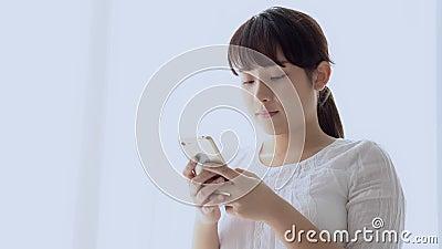 A posição de sorriso da mulher asiática nova bonita do retrato que olha o telefone celular esperto que lê a rede social com aprec vídeos de arquivo