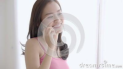 A posição de sorriso da mulher asiática nova bonita para relaxar no quarto, menina que usa a fala esperta móvel do telefone aprec video estoque