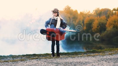 Posição pequena feliz da menina do aviador perto do lago no traje plano do cartão com o fumo azul da cor que joga o movimento len vídeos de arquivo