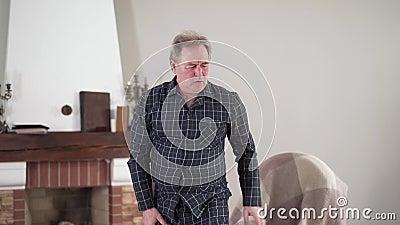 Positieve volwassen blanke man die opstaat vanaf de stoel en neerzit vanwege plotselinge scherpe pijn in de rug Gezondheid stock video