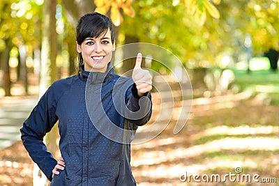 Positiv kvinnligidrottsman nen med tum upp