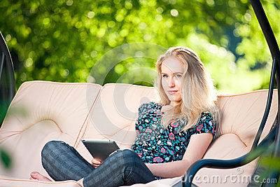 Positive beautiful young woman using tablet
