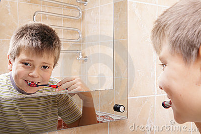 Positive boy brushing teeth reflection
