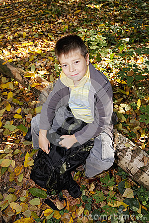 Positive boy sitting on log