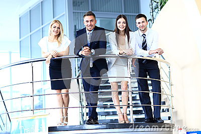 Positive business group standing on stairs of modern office