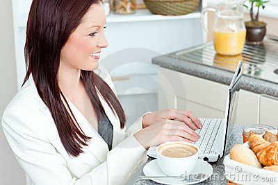Positive businesswoman using her laptop at home
