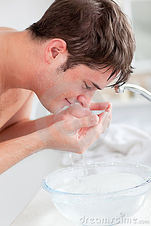 Positive caucasian man spraying water on his face